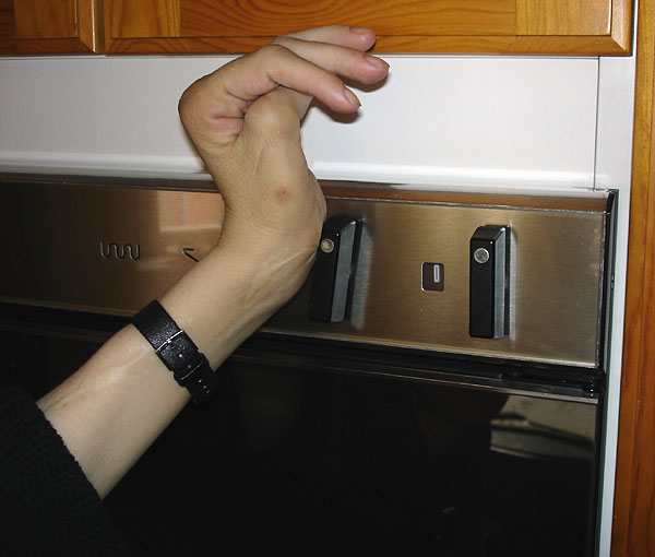User turns on oven by pressing against knob with palm