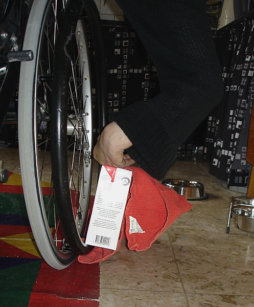 The user leans the milk carton against the wheel and positions the towel underneath it.