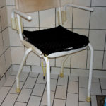 Shower chair with soft back and swinging armrest