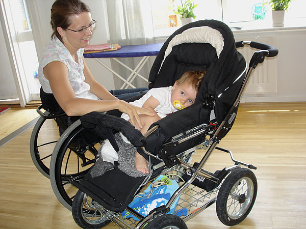 User sits next to stroller; stroller and wheelchair are same height