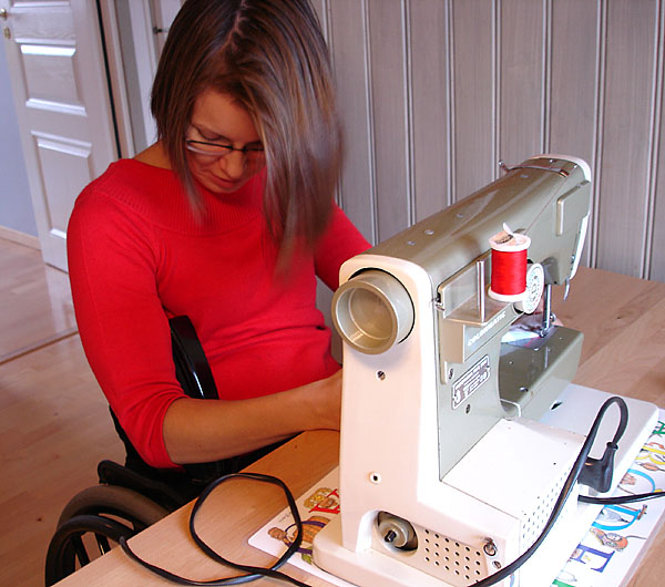 User controls sewing machine with pedal tucked under arm