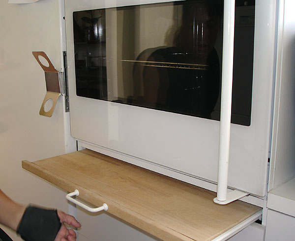 Oven with side-hinged oven door and vertical handle; pull-out board below
