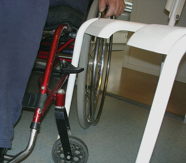 Shower stool locked to wheelchair with wheelchair brake