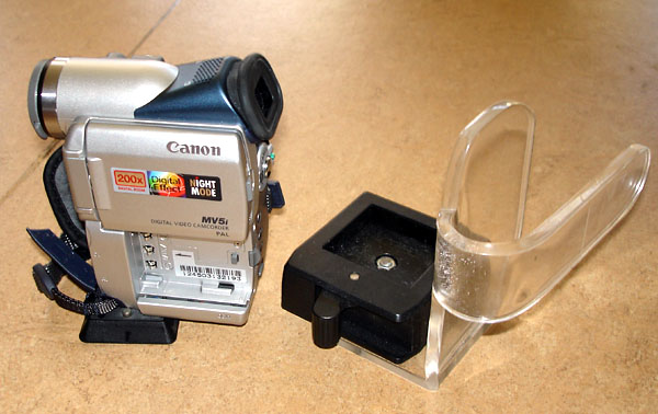 Video camera holder attached to plexiglas handle; camera stands next to it