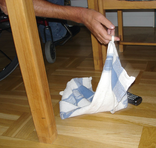 User hits object (phone) under table with towel to bring it closer