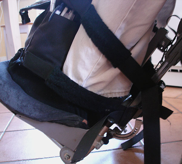 Padded straps around calf and wheelchair leg support