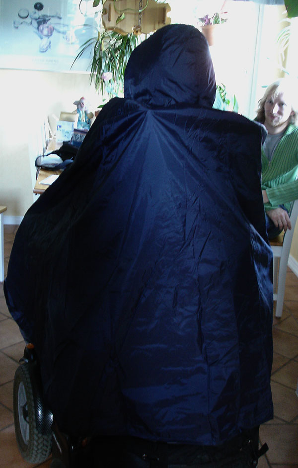 User with rain poncho from the back – the back of the wheelchair is also protected