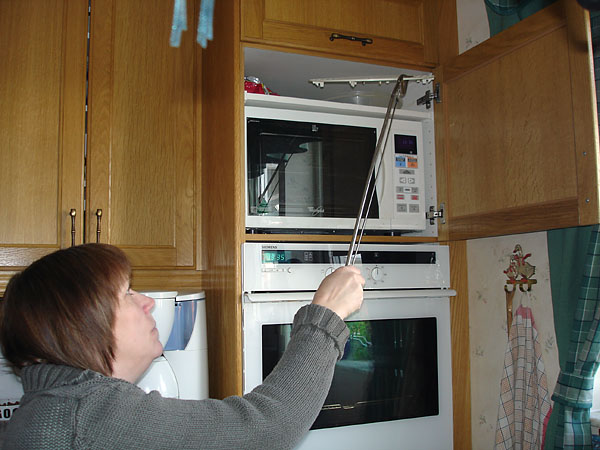 User gets a dish from the upper cabinet using pliers