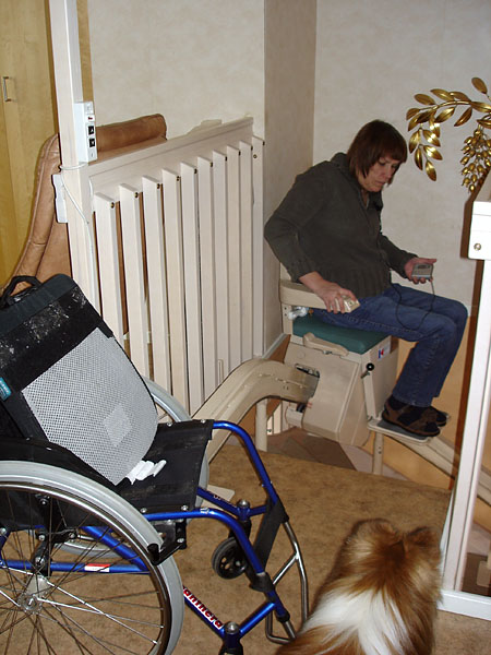 User on chair stairlift on upper story