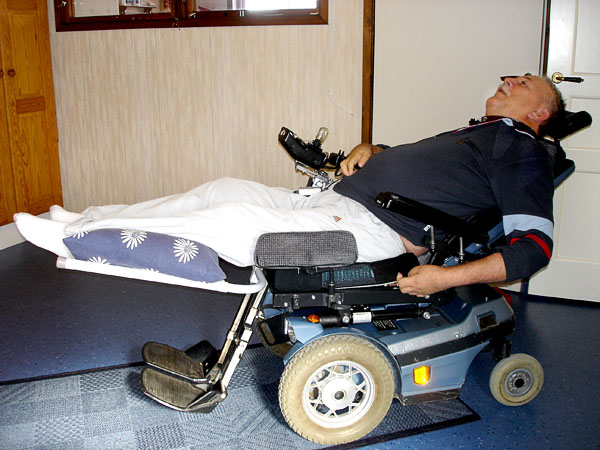 User lying in wheelchair with leg rest attached
