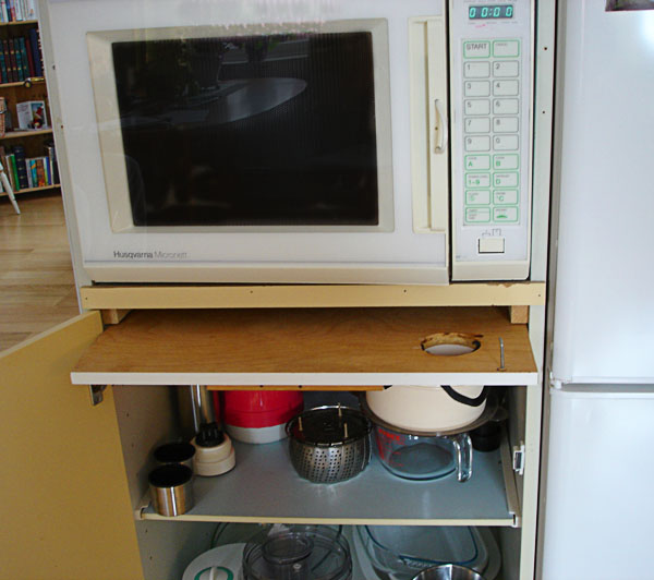 Microwave with pull-out board underneath