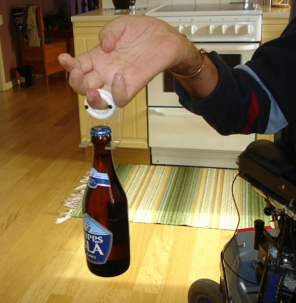 User holding a bottle with ring finger in the device's ring