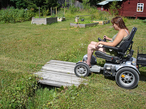 The user drives on a wooden ramp over a ditch
