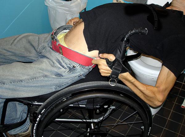 Dra upp byxor sittande i rullstolen