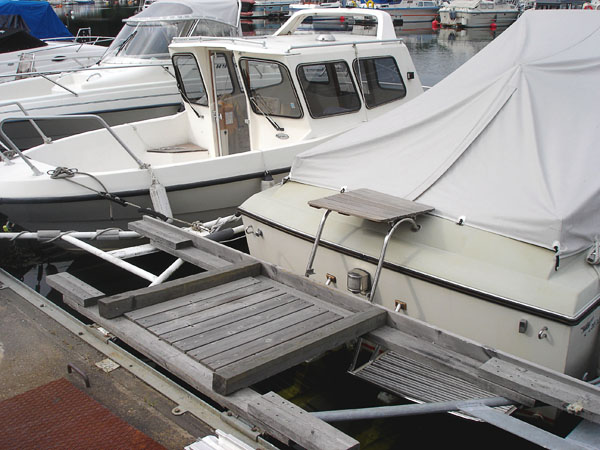 Boat with platform on swimming ladder at dock