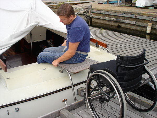 User sitting on platform and moving legs into boat
