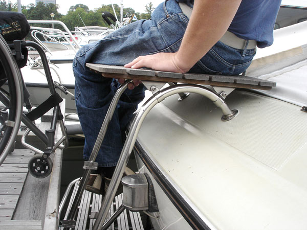 User sits on platform on the boat's swimming ladder