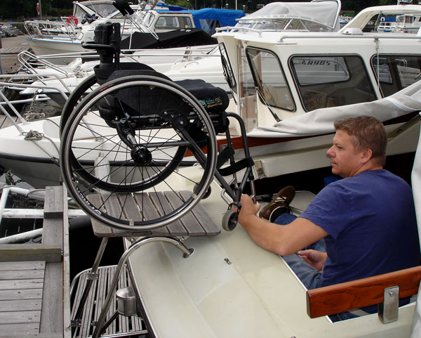 User lifts wheelchair onto the boat