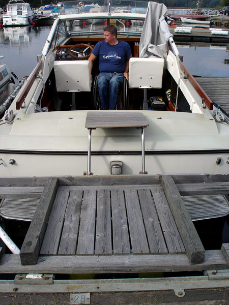 Boat with platform on swimming ladder at dock; user sitting on boat