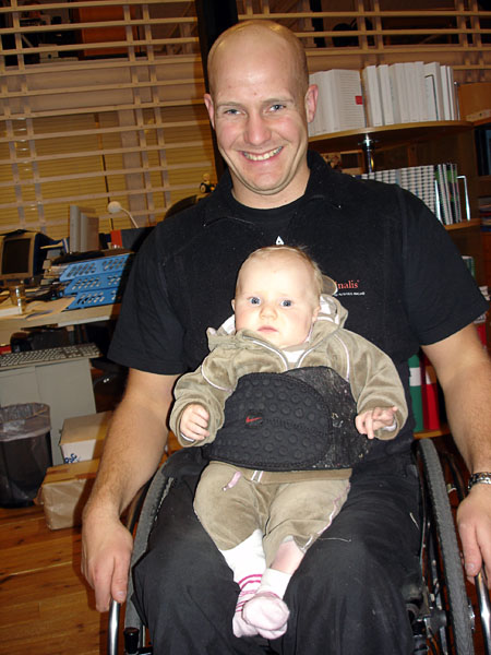 User with daughter on lap with a soft corset around him and the child