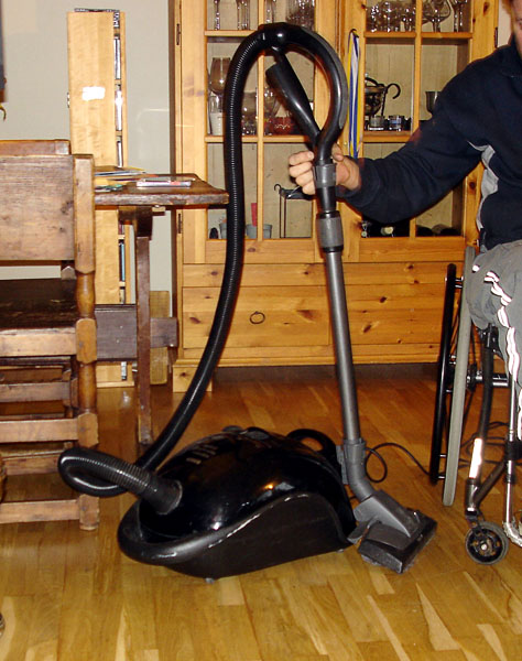 User attaches tube to vacuum cleaner