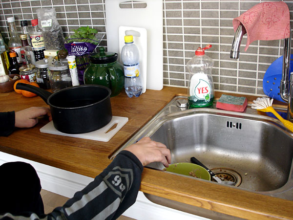 User moves cutting board with pot to sink
