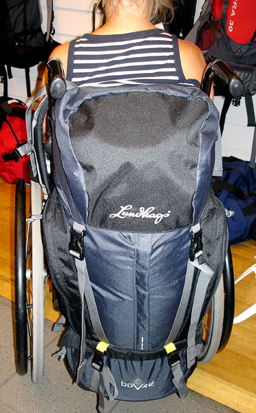 Large backpack for travel suspended from the wheelchair handles (viewed from behind).  Please note that the person in this photo is the tipster