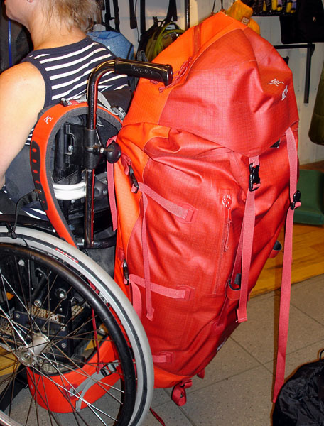 Different model, large backpack for travel suspended from the wheelchair handles (viewed from the side). Please note that the person in this photo is the tipster