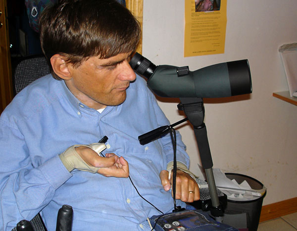 Binoculars on stand with holder on wheelchair