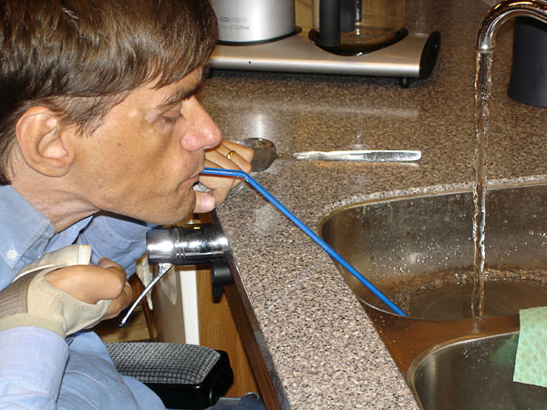User drinks water through straw from sink