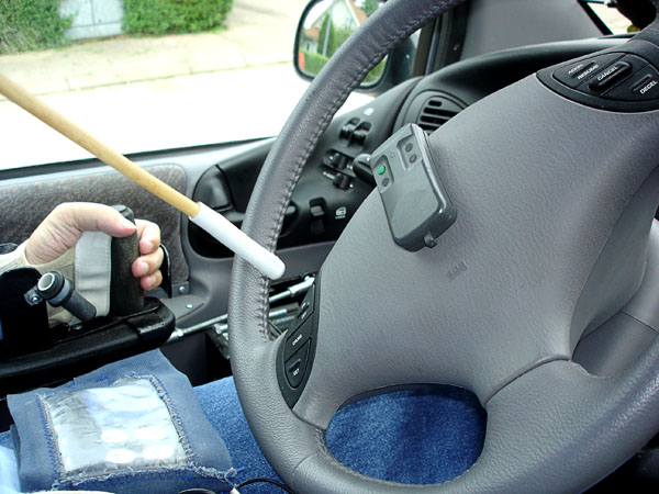 User presses on transmitter on steering wheel with mouth stick