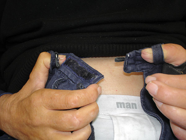 User places thumbs in waistband belt loops