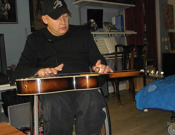 User with slide guitar on lap