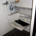 Wall-mounted shower stool with armrest