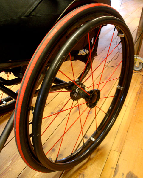 Wheelchair wheel with red tires and spokes