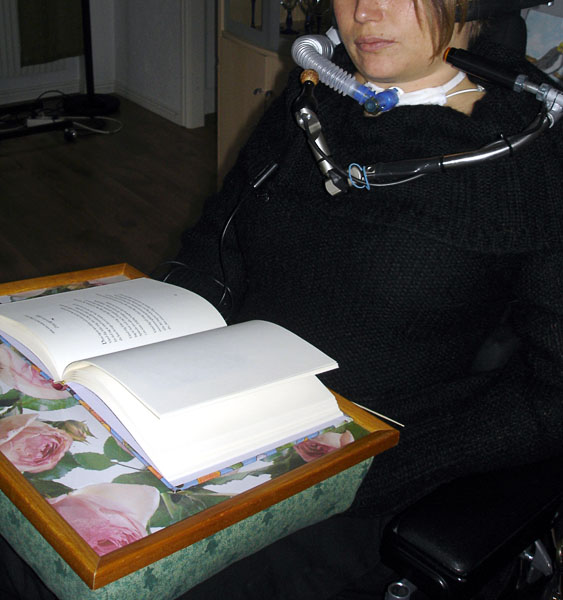 User with book cushion on lap