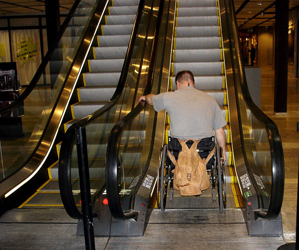 Ride on escalator with manual wheelchair