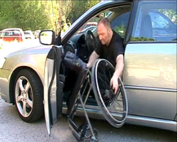 Lifting a wheelchair out of a passenger car