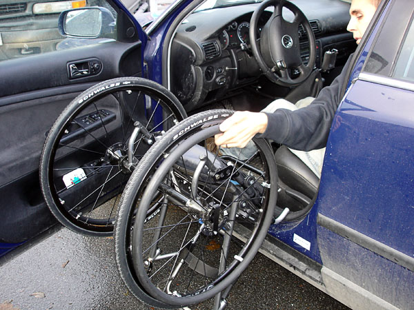 User tilts wheelchair on foot bar