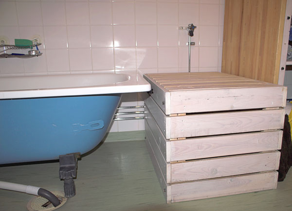 Bathtub without front and with crate next to it