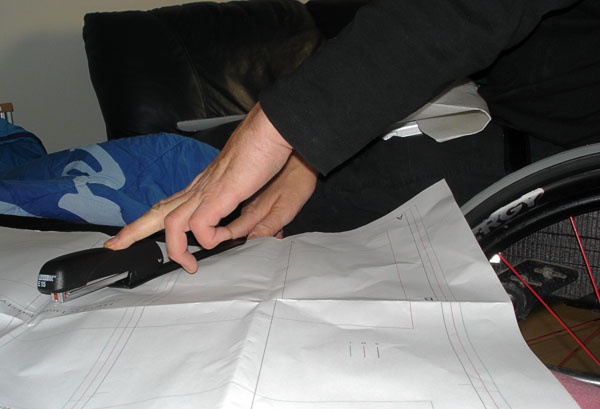 User staples fabric and pattern together with stapler