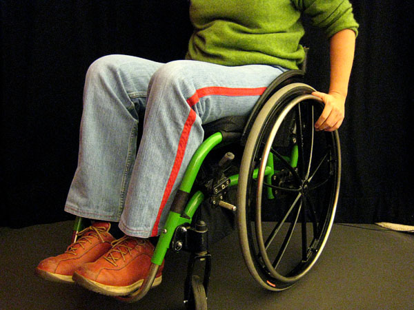 User sitting in a green wheelchair