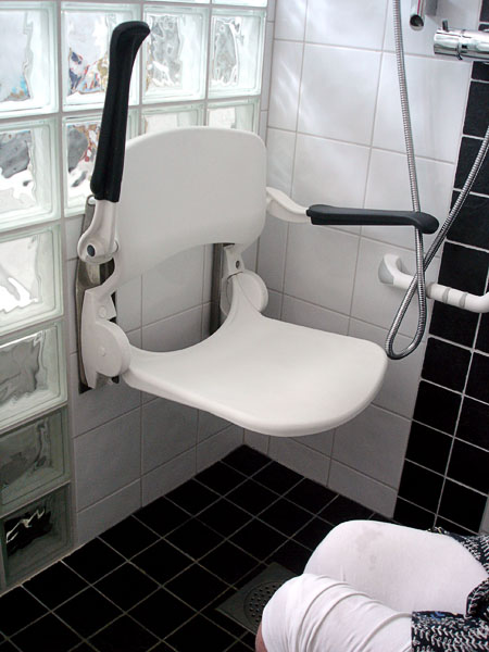 Shower chair with one armrest folded up