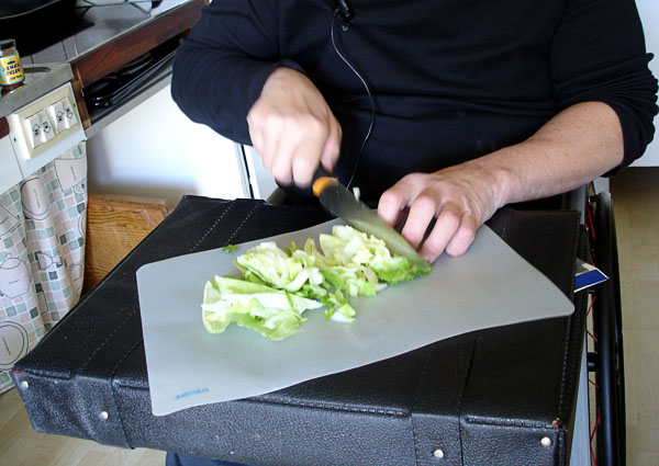 User prepares salad with the suitcase as a work surface