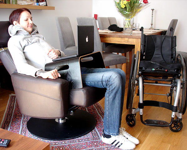 User working while sitting in her armchair