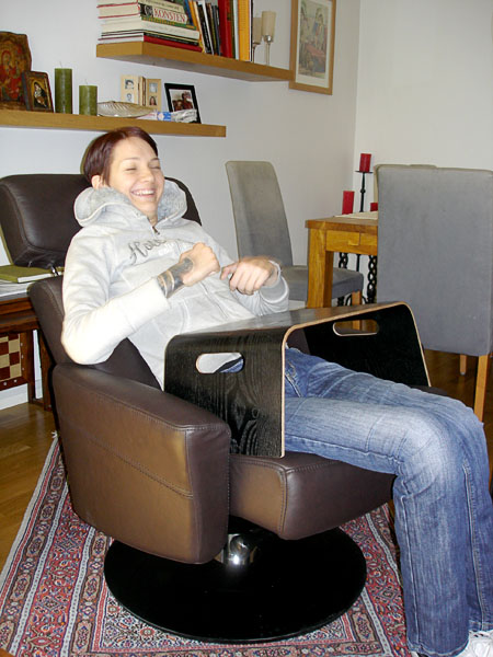 User in her armchair with computer on bed tray