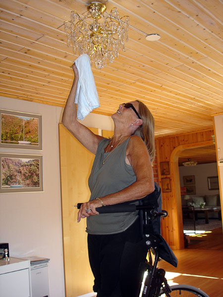 User washes a chandelier while standing in the standing wheelchair (close-up)