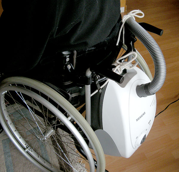 User with vacuum cleaner attached to the wheelchair. Photo: Olle Kohls