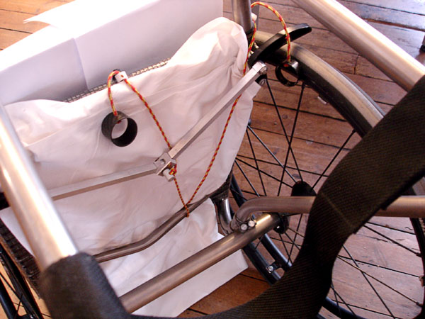 Wheelchair with brake handle and brake cord from below (wheelchair is covered by a sheet to be able to see the brake cord better)