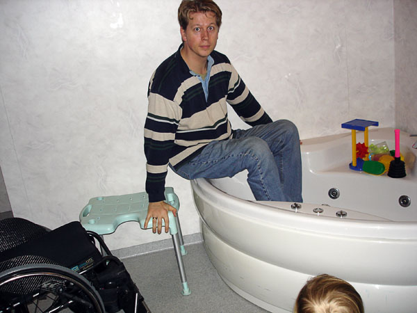 User sits on edge of tub